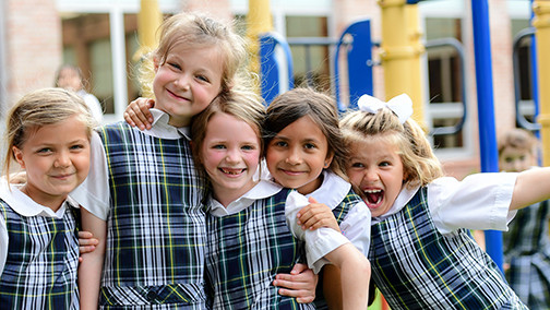 Lower school girls smiling on playground