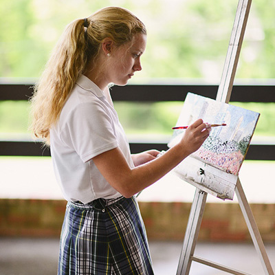 Girl student painting on easel